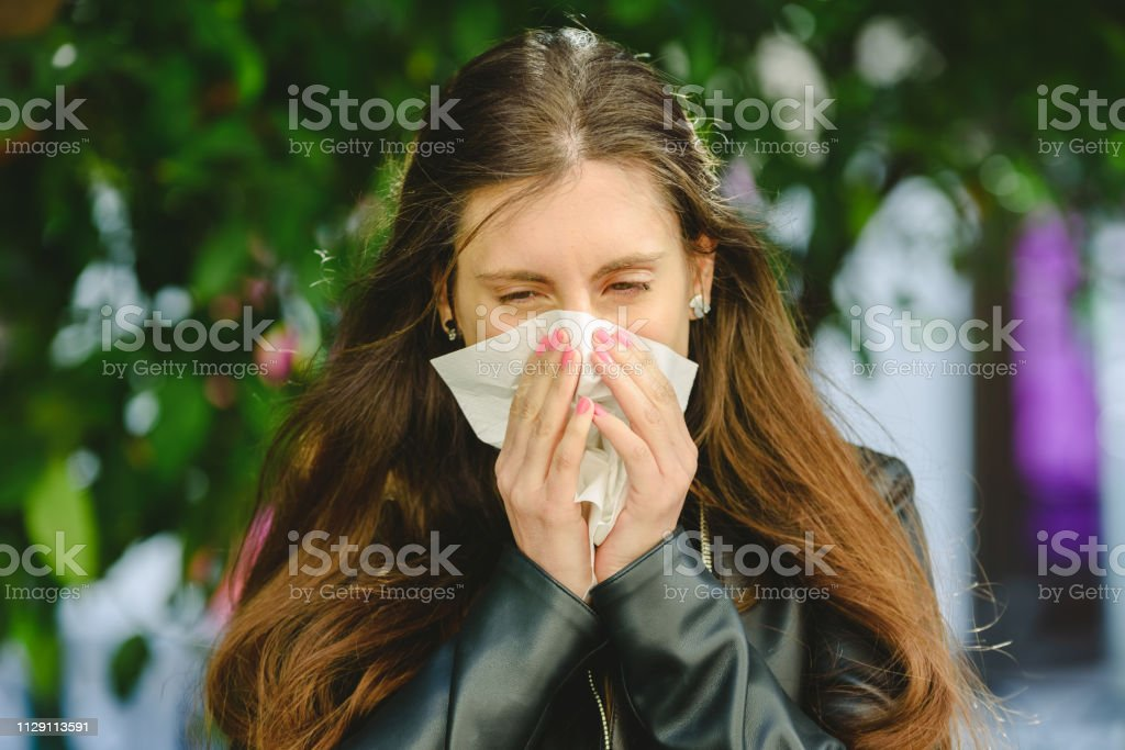 Young woman blowing her nose affected by spring allergy to pollen in...