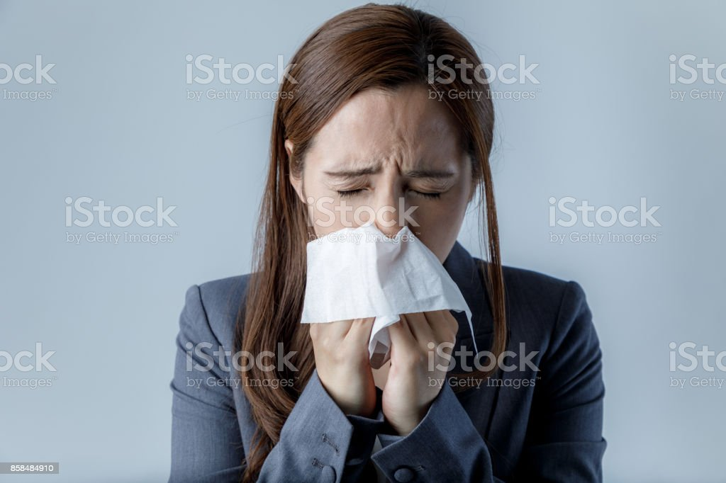young woman blowing her nose. allergic rhinitis. hay fever. stock photo