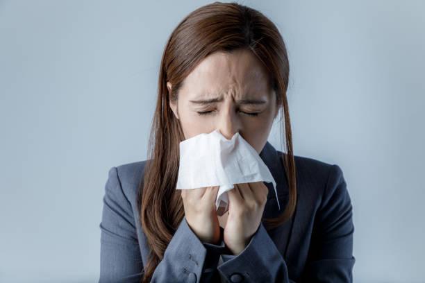 若い女性が彼女の鼻を吹きます。アレルギー性鼻炎。花粉症。 - くしゃみ 日本人 ストックフォトと画像