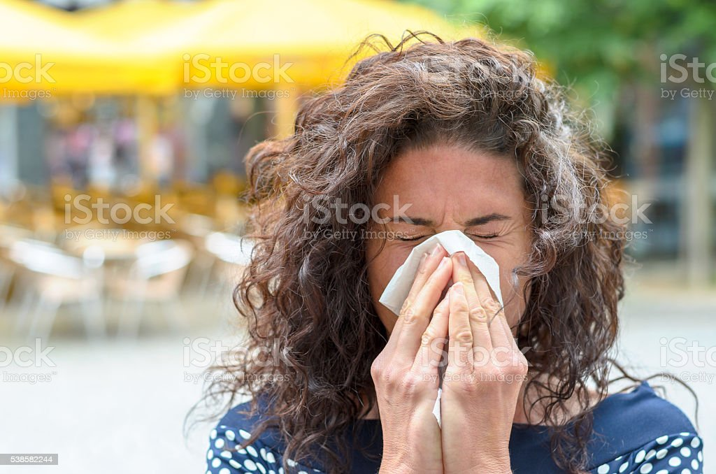 Young woman blowing her nose in an urban square stock photo