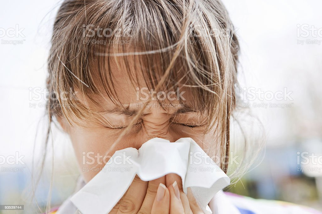 A young woman blowing her nose outdoors stock photo