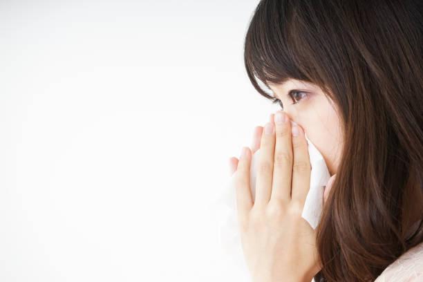 若い女性は彼女の鼻をかむ - くしゃみ 日本人 ストックフォトと画像
