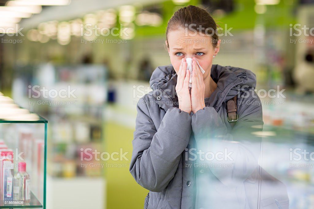 Young woman blowing her nose while in a modern pharmacy stock photo