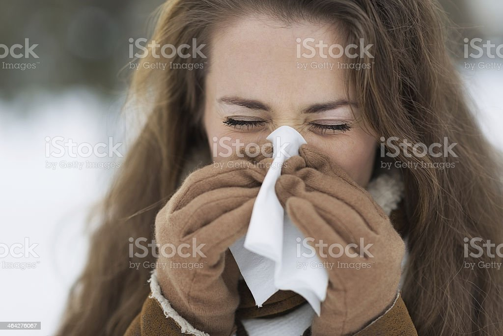 young woman blowing nose in winter outdoors stock photo