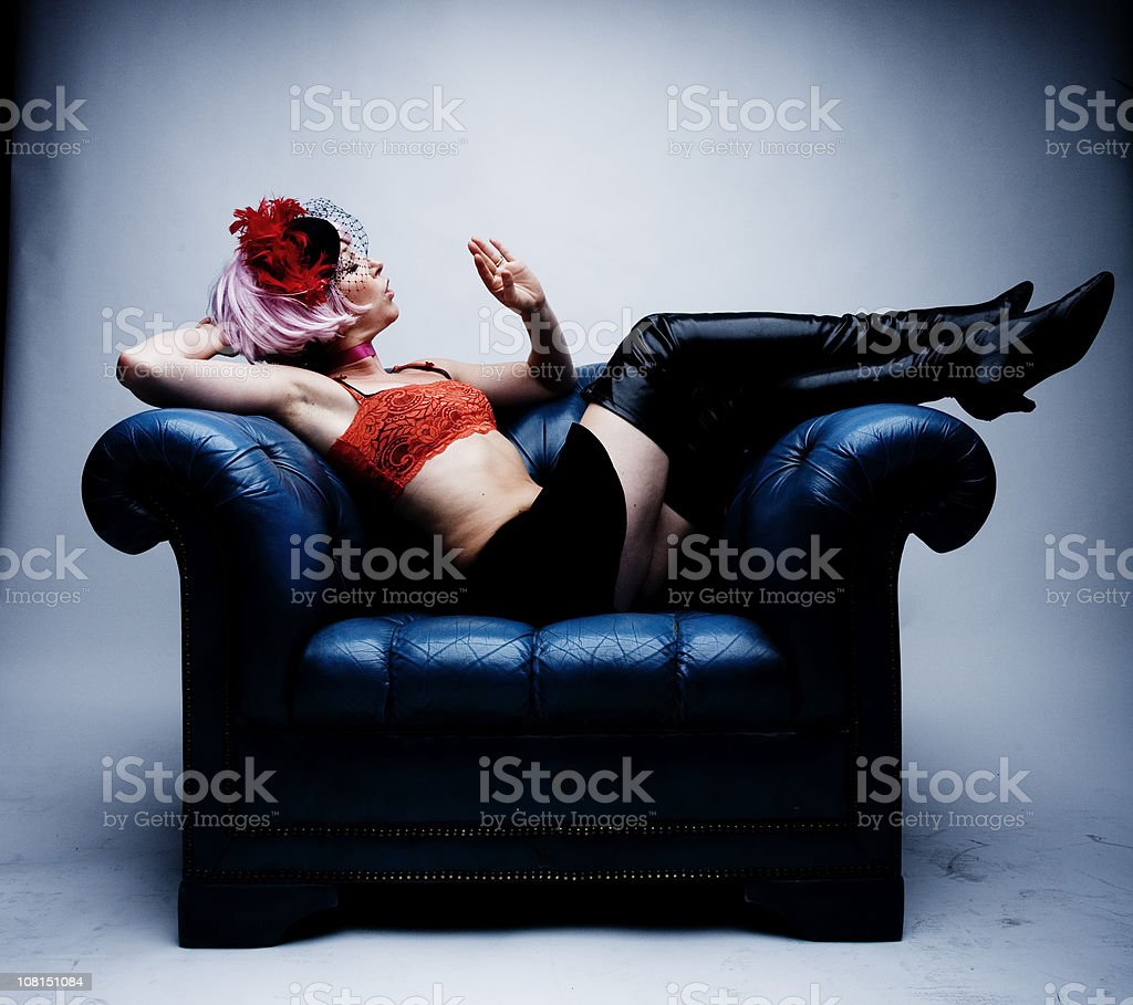 Young Woman Blowing on Her Nails Sitting Armchair royalty-free stock photo