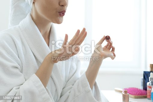 Young woman blowing on nails after applying nail polish.