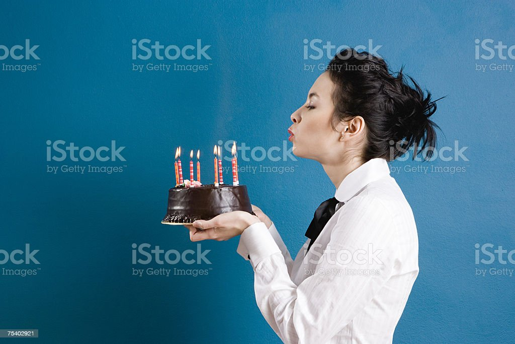 Young woman blowing out birthday candles stock photo