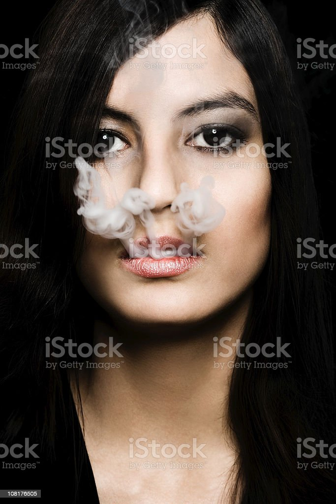Young Woman Blowing Smoke From Mouth stock photo