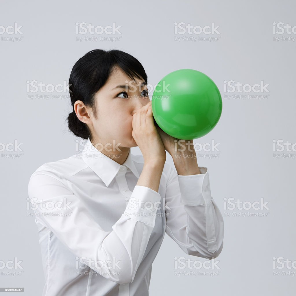 Young woman blowing up a balloon stock photo