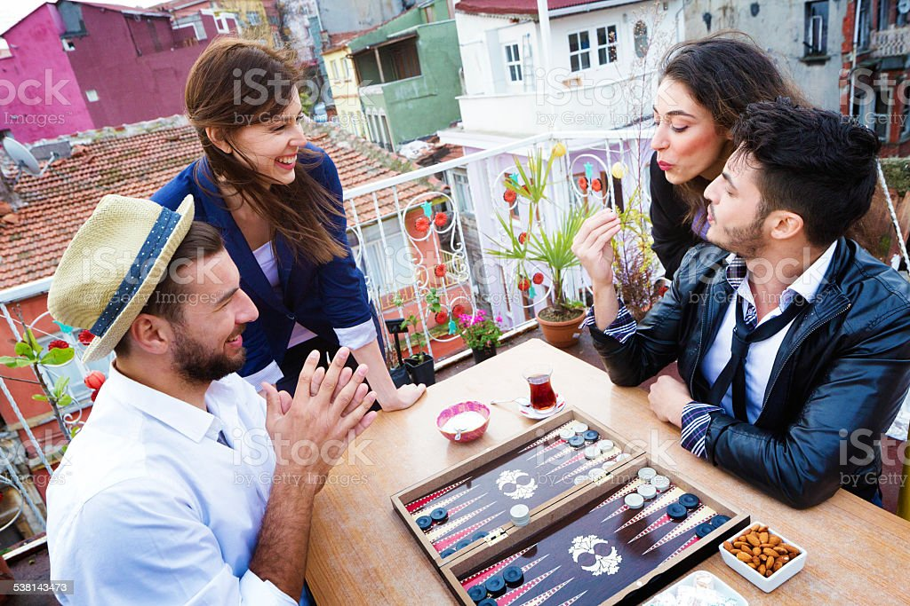 Young woman blows on dice for luck during backgammon game stock photo