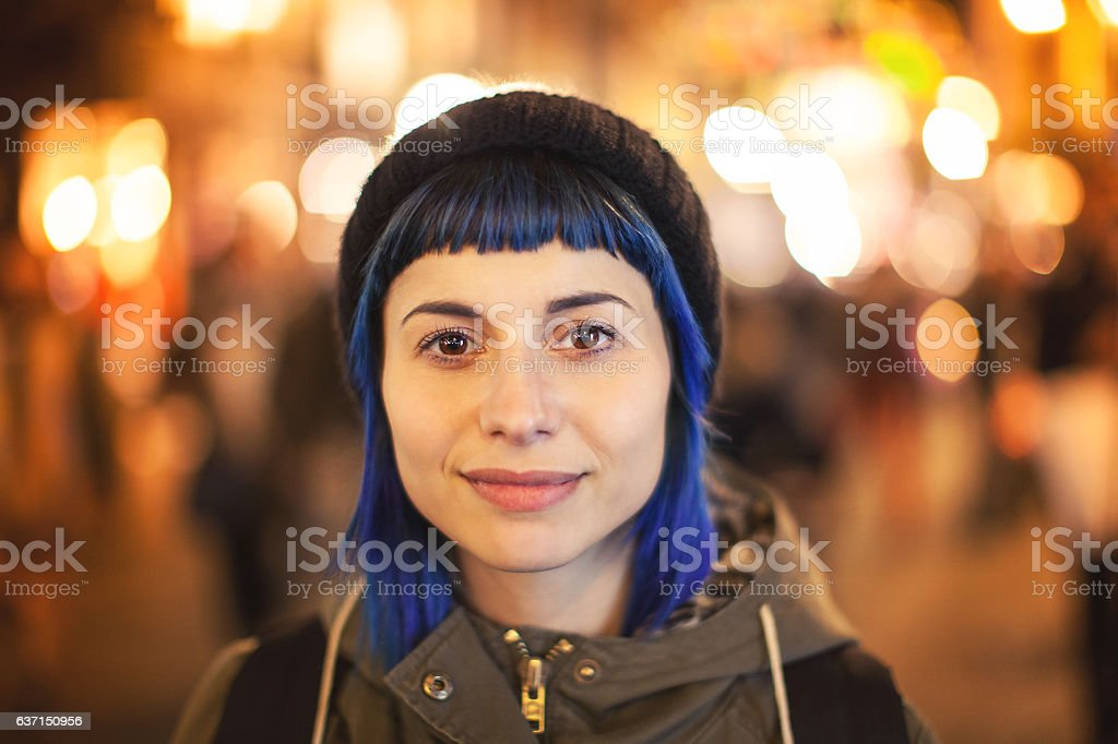 Young woman bluehair walking through citylight - Photo