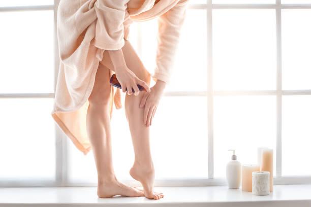 junge frau körperpflege zu hause drinnen - bein make up stock-fotos und bilder