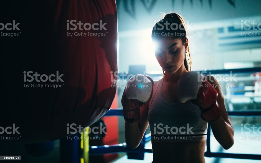 Young woman boxer concentrating before hitting the punching bag stock photo