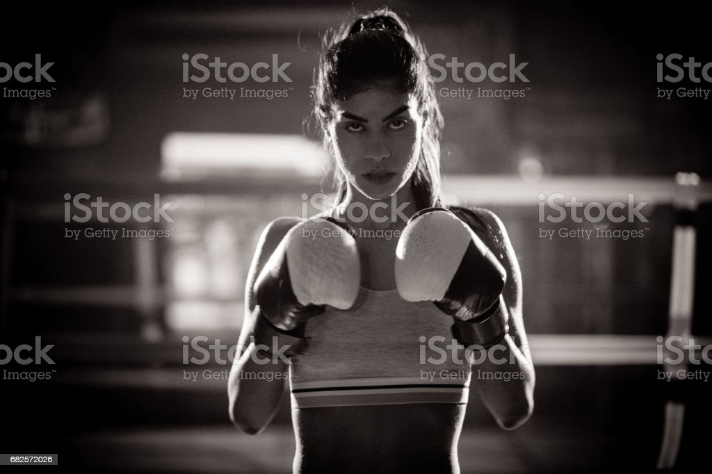 Young woman boxer ready to fight in the boxing ring stock photo