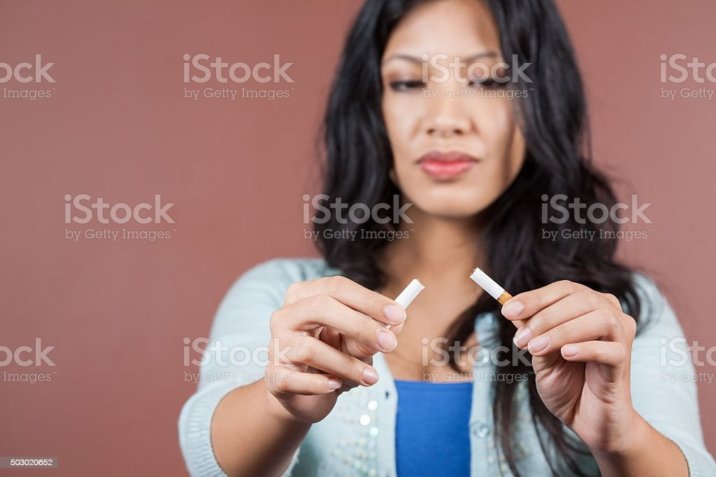 Young woman breaking her cigarette habit stock photo