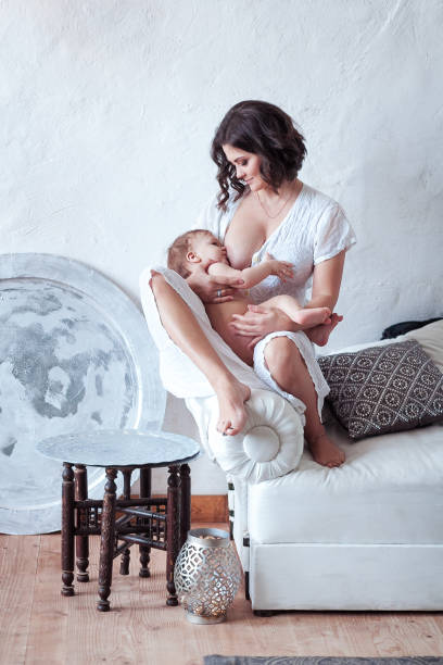 A young woman breast-feeding baby sitting on sofa with white rustic wall background stock photo