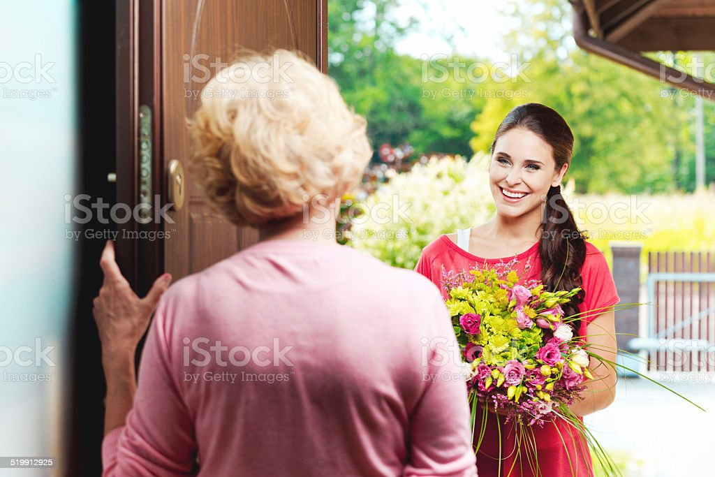 Young woman bringing birthday flowers to her grandmother Happy young woman bringing birthday flowers to senior woman, standing at the entrance door and smiling.  20-24 Years Stock Photo