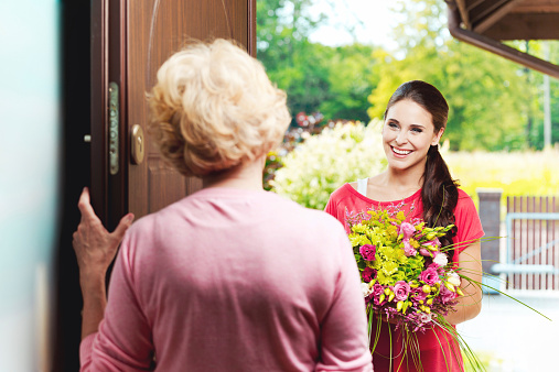 Young Woman Bringing Birthday Flowers To Her Grandmother Stock Photo - Download Image Now
