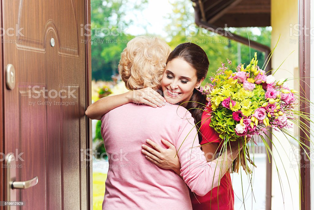 Young woman bringing birthday flowers to her grandmother Happy young woman bringing birthday flowers to senior woman, standing at the entrance door and hugging.  20-24 Years Stock Photo