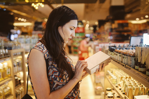 Image of a young brunette woman, browsing through the shelves of a Bangkok shopping mall, looking for natural cosmetics.