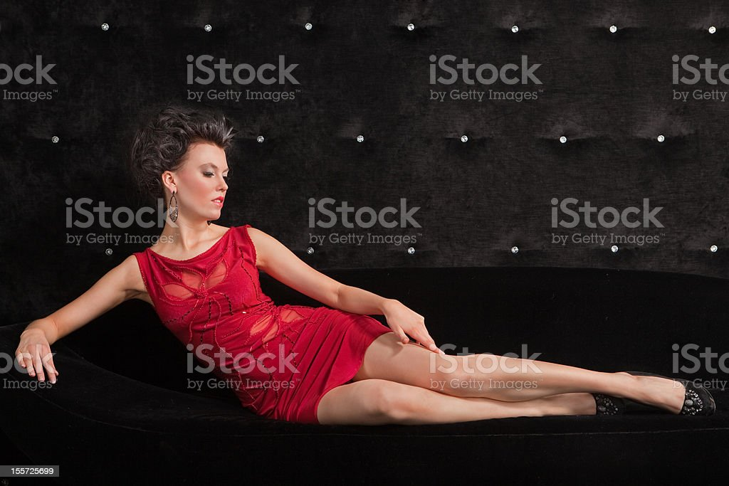 Young woman brunette in red dress laying on black sofa royalty-free stock photo