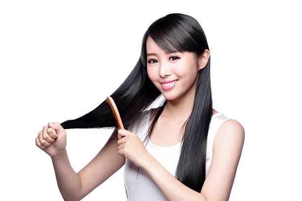 schöne junge frau, die ihr haar bürsten - frisuren für schulterlanges haar stock-fotos und bilder