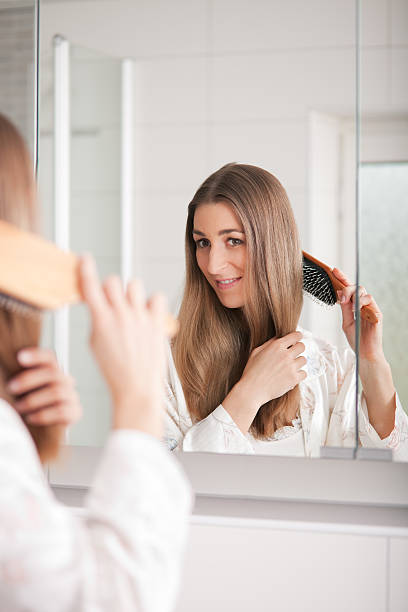 Young woman brushing hair in front of mirror stock photo