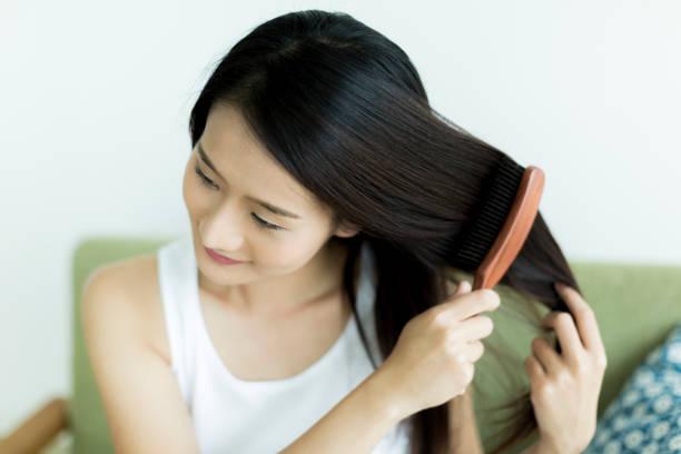 若い女性ブラッシング髪 - people of color ストックフォトと画像