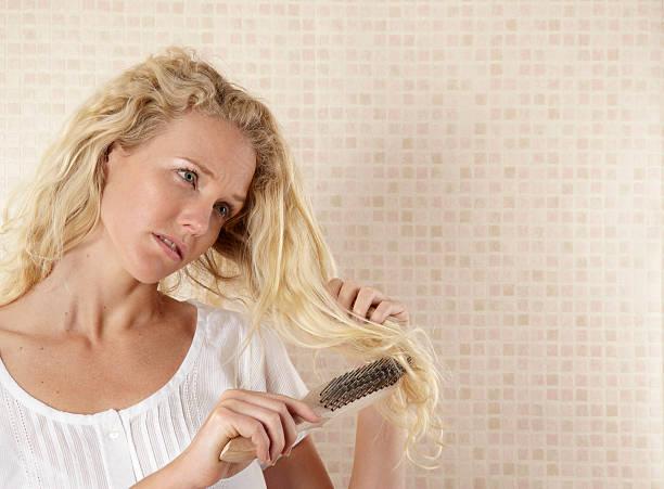 Young woman brushing hair with DIY metal brush stock photo