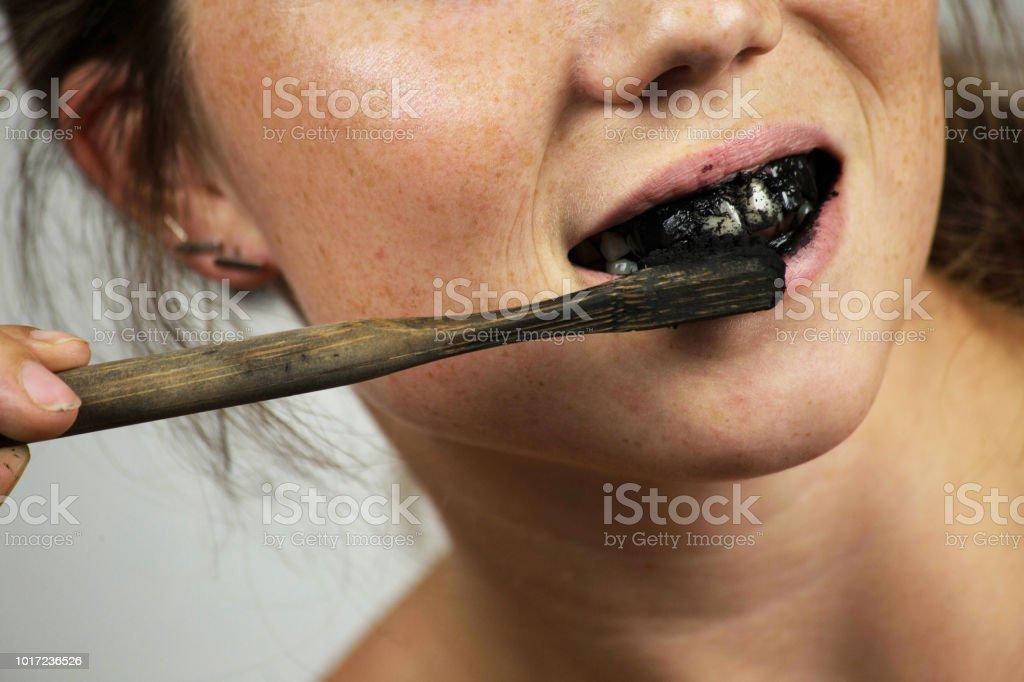 junge Frau, die ihre Zähne mit einer schwarzen Zahnpasta mit Aktivkohle, und schwarze Zahnbürste auf weißem Hintergrund für Zähne Bleaching – Foto