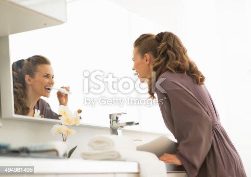 istock young woman brushing teeth in bathroom 494961495