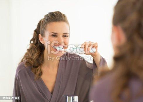 istock young woman brushing teeth in bathroom 495335209