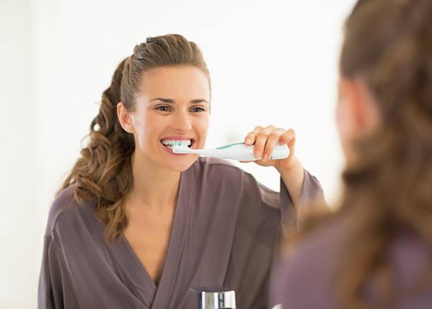 young woman brushing teeth in bathroom stock photo