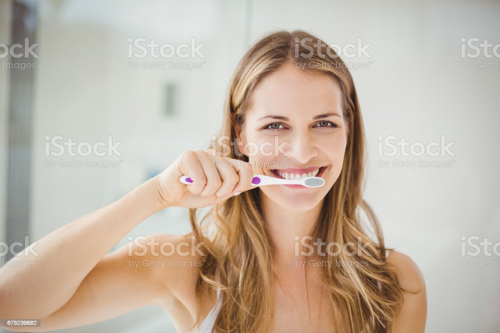 Young woman brushing teeth stock photo