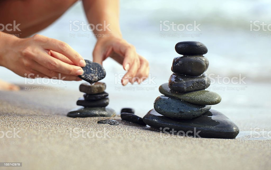 Young woman building stone tower at the beach stock photo