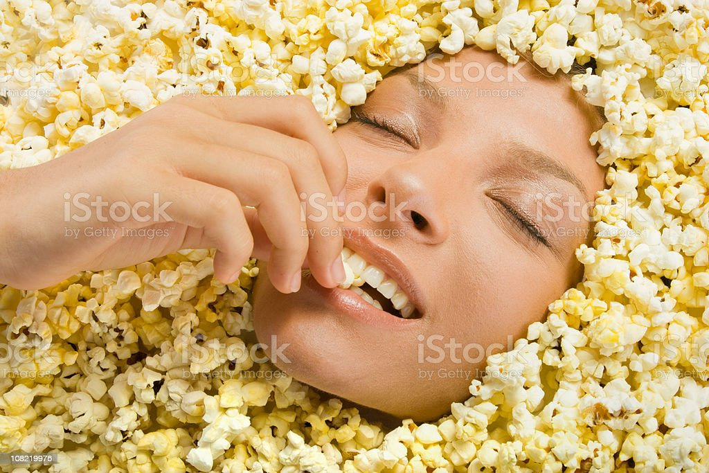 Young Woman Buried in Popcorn and Eating It stock photo
