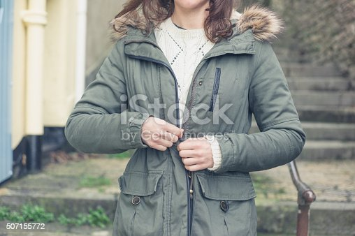 A young woman is standing outside and is buttoning her coat