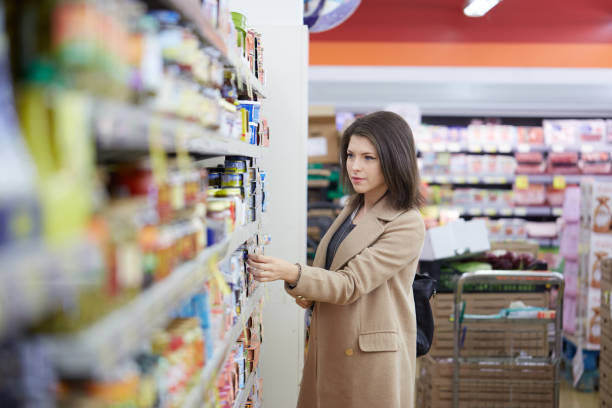 young woman buy can of tuna at supermarket stock photo