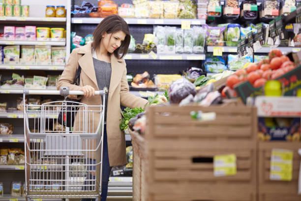 junge frau kaufen obst und gemüse im supermarkt - bio lebensmittel stock-fotos und bilder