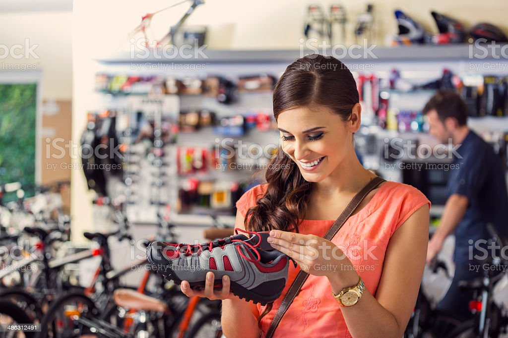 Young woman buying a cycling shoes royalty-free stock photo