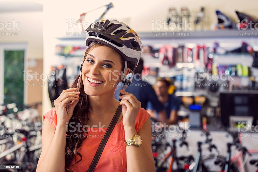 Young woman buying a helmet Portrait of young woman trying on a bicycle helmet in bike shop and smiling at camera. 20-24 Years Stock Photo