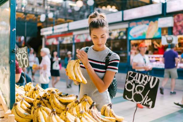 young woman buying bananas at the market - targ handel detaliczny zdjęcia i obrazy z banku zdjęć