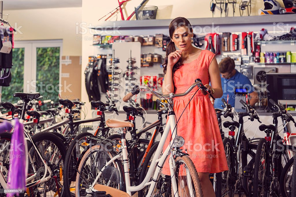 Young woman buying bicycle Young woman watching a bicycle in a bike store. Adult Stock Photo