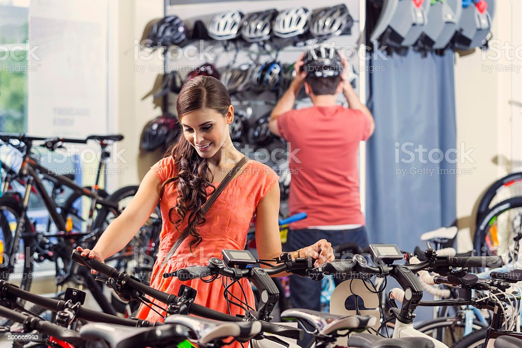 Young woman buying bicycle Young woman watching a bicycle in a bike store with a man wearing sports helmet in the background. Adult Stock Photo