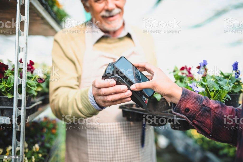 Junge Frau Blumen kaufen und bezahlen mit ihrem Smartphone – Foto