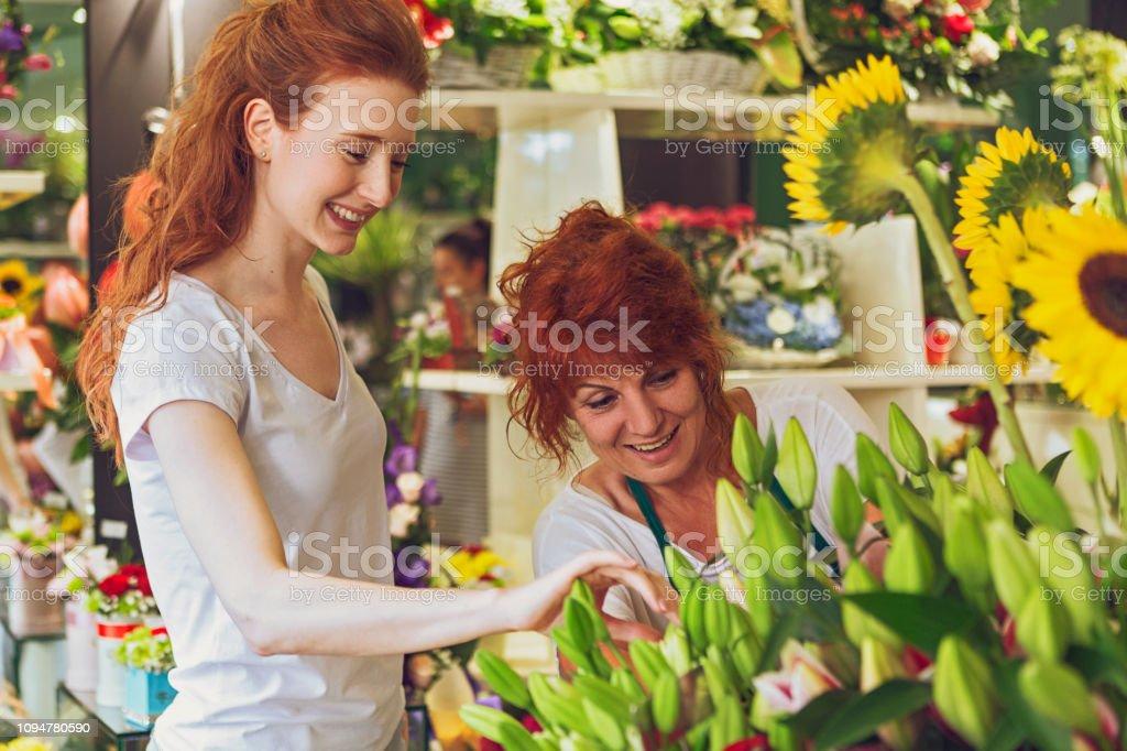 Mature florist woman serving a customer in flower shop