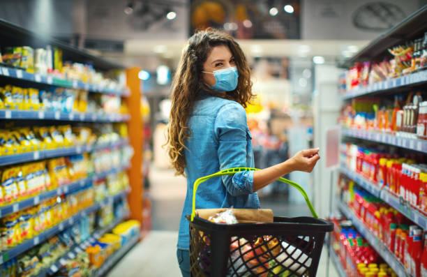 Young woman buying food at a supermarket during coronavirus pandemic. stock photo