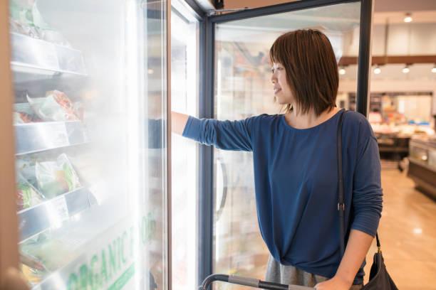 jovem mulher comprando alimentos congelados - comida congelada - fotografias e filmes do acervo