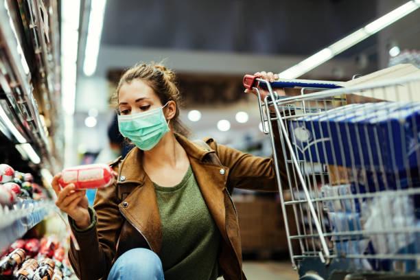 ung kvinna som köper matvaror medan hon bär ansiktsmask i snabbköpet. - supermarket bildbanksfoton och bilder