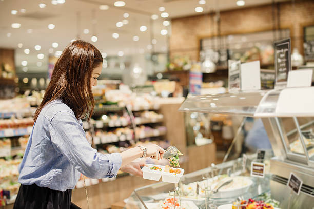 young woman buying grocery in supermarket - delis stock photos and pictures